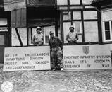 Sgt. Mallory J. Kocopina, W. Aliquippa, PA & Sgt. Worner W. Kahl, Detroit MI., Put out a welcome  sign for the 100,000th prisoner taken by the 1st Division, U.S. First Army.